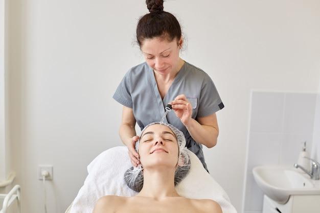 Позитивный косметолог работает в салоне красоты.
