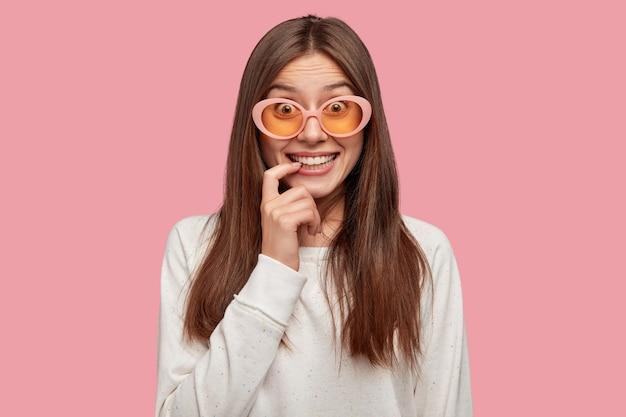 분홍색 벽에 포즈 긍정적 인 아름 다운 갈색 머리