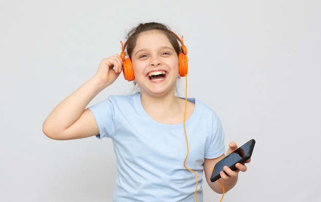 Positive beautiful caucasian little girl wearing jeans overall over white background holds modern cell phone connected to headphones, clenches fist from good emotions, exclaims with joy,