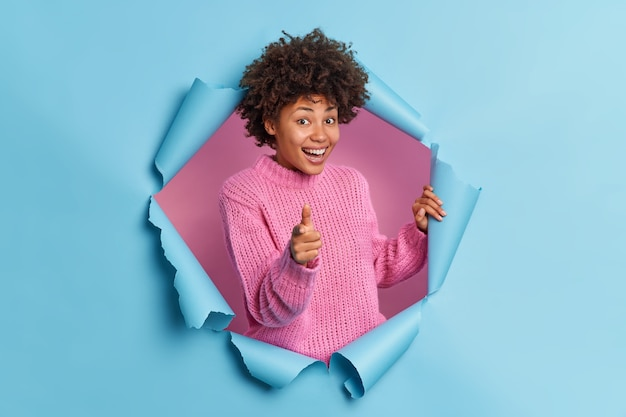 Positive beautiful curly ethnic woman makes you got this gesture praises good job points at you encourages person smiles gladfully wears knitted sweater breaks through blue paper wall