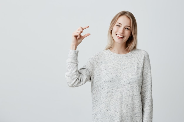 Positive beautiful fair-haired female in loose sweater shows something small in size with hands, has good mood