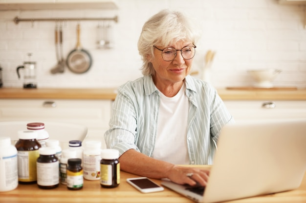 Positive beautiful gray haired female pensioner in spectacles choosing healthy lifestyle, sitting in kitchen with dietary supplements, keyboarding on laptop, typing review via online store