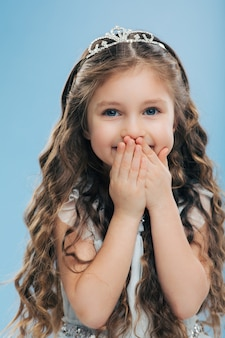 Positive beautiful smiling child keeps both hands on mouth