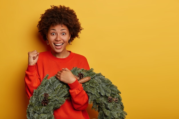 Positive beautiful woman clenches fist, anticipates for result, carries firtree wreath laughs happily, dressed in red jumper stands over yellow studio wall blank space for advertising