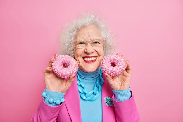 陽気な美しいしわの多いヨーロッパの女性は、2つのおいしい艶をかけられたドーナツを持ち、笑顔を広く持ち、気分が良く、おしゃれな服や宝石を化粧する