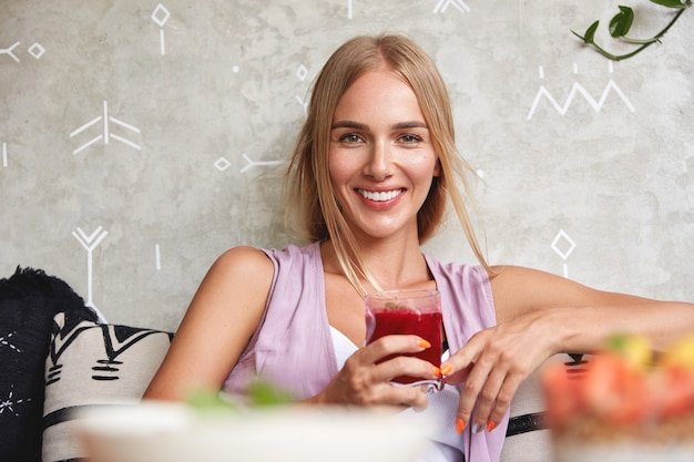 Positive beautiful young female model feels relaxed while sits on comfortable sofa in cafe, enjoys fresh strawberry smoothie, recreate during summer holidays. people, rest and lifestyle concept