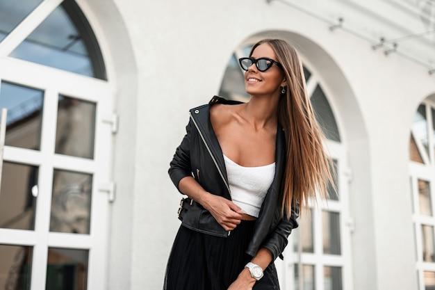 흰 셔츠에 세련 된 블랙 재킷에 유행 선글라스에 긍정적 인 아름 다운 젊은 hipster 여자 빈티지 화이트 건물 근처 거리에 달려있다. 유행 행복 소녀 모델 야외에서 이완.
