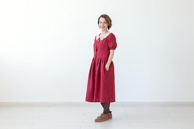 흰색 배경에 빨간색 겸손한 드레스를 입고 포즈를 취하는 긍정적인 아름 다운 젊은 웃는 여자. 세련 된 어린 소녀의 개념입니다.