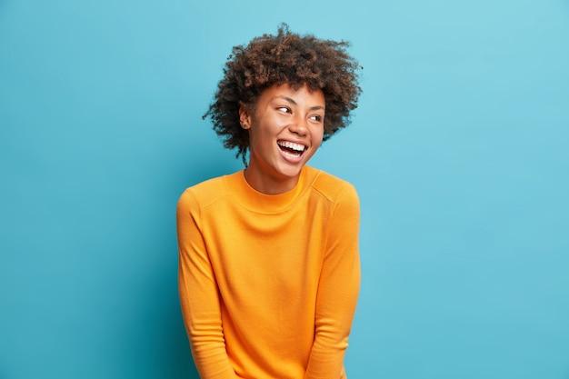Позитивная красивая молодая женщина, язвительно смеется, смотрит в сторону с беззаботным выражением лица, носит повседневный оранжевый свитер, изолированный на синей стене студии