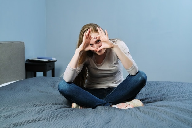 Положительная красивая молодая женщина, показывающая руки, подписывает сердце символа, сидя дома на кровати. эмоции любви, счастья, радости, дня святого валентина, концепции молодых людей