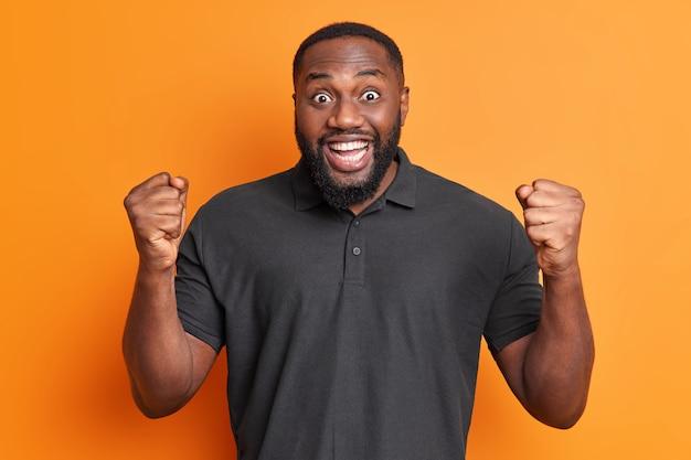 긍정적 인 흑인 성인 남자는 예 제스처를 쥐고 주먹이 챔피언 또는 승자가 생생한 주황색 벽 위에 고립 된 캐주얼 검은 색 티셔츠를 입는 것처럼 느끼게합니다.