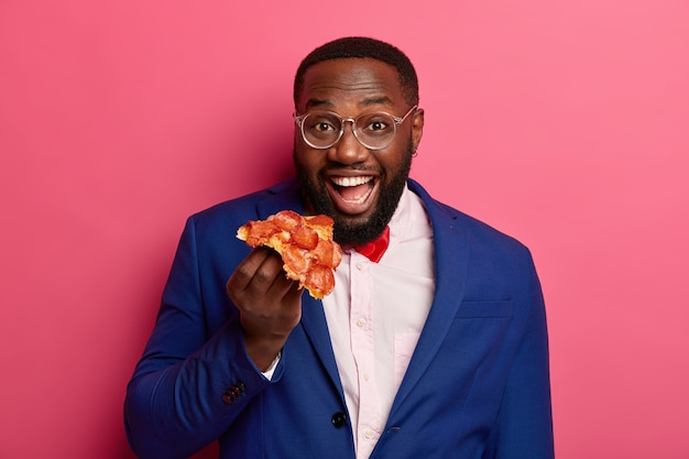 긍정적 인 검은 수염을 가진 남자는 피자 한 조각을 먹고, 공식적인 옷과 투명한 안경을 쓰고, 식욕이 좋고 건강에 해로운 간식을 가지고 있습니다.