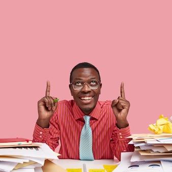 Imprenditore nero positivo indica con entrambi gli indici verso l'alto, soddisfatto dell'accordo firmato con successo, vestito in modo formale, siede al desktop