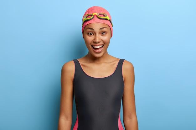 Позитивный черный инструктор по плаванию в купальнике, шапочке и очках