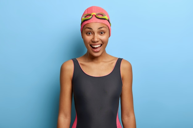Istruttore di nuoto femminile nero positivo vestito in costume da bagno, cuffia da bagno e occhiali