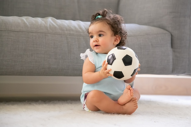 Positive black haired baby girl in pale blue clothes sitting on floor at home, looking away, playing soccer ball. copy space. kid at home and childhood concept