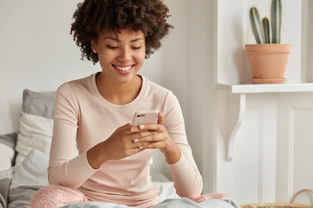 Positive black lady with afro haircut, holds modern cellular, reconsiders text message recieved from friend, types feedback, dressed in nightclothes, sits at comfortable bed alone, has lazy day