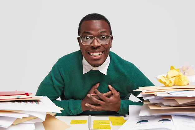 Positive black male worker does paper work, studies for examination at college, keeps both hands on chest and smiles sincerely, looks through spectacles