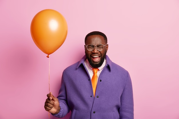 Positive black man with beard holds inflated orange balloon in hand, exclaims emotionally, going on party
