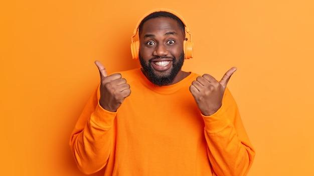 굵은 수염을 가진 긍정적 인 흑인 남자는 제스처처럼 엄지 손가락을 유지하며 헤드폰에서 좋아하는 트랙 목록을 즐깁니다. 생생한 주황색 벽 위에 절연 된 캐주얼 긴팔 점퍼