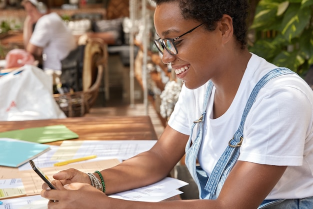Positive black young woman with cheerful expression, uses modern technology and wifi for checking email box