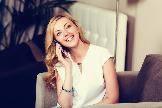 Positive blond girl speaking mobile phone at home