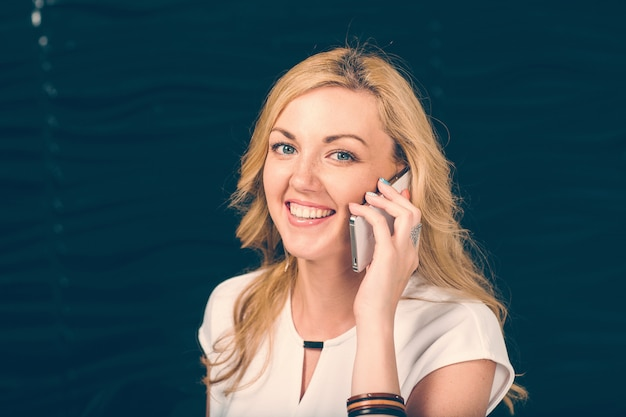 Positive blond girl talking mobile phone and smile