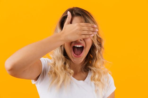 黄色の壁に隔離された手で目を覆う基本的な服を着たポジティブなブロンドの女性