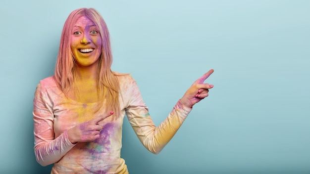 Positive blonde female dirty with colorful powder, advertises something on blank space, smiles happily, enjoys indian fest, isolated against blue wall. promotion concept