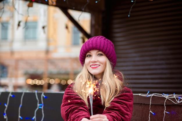 キエフのクリスマスフェアで輝く線香花火を持って、スタイリッシュな服を着たポジティブなブロンドの女の子