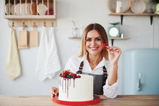 Позитивная блондинка в помещении со своим домашним пирогом держит фрукты.