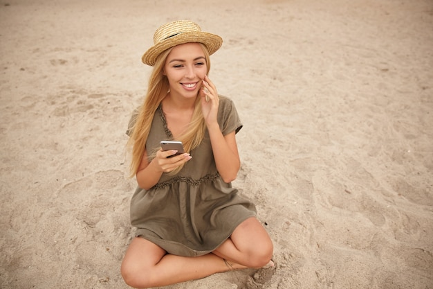 Позитивная блондинка с длинными волосами, симпатичная женщина, сидящая на песке со скрещенными ногами, держа смартфон в руке и широко улыбаясь, касаясь ее лица поднятой рукой