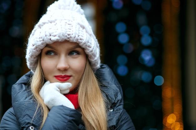 花輪の背景の上の通りで冬の休日を楽しんでいる赤い唇を持つポジティブな金髪モデル