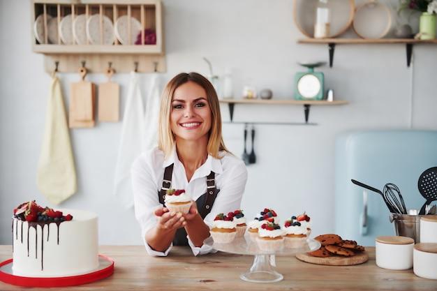 Позитивная блондинка с домашним вкусным печеньем и пирожным на кухне.