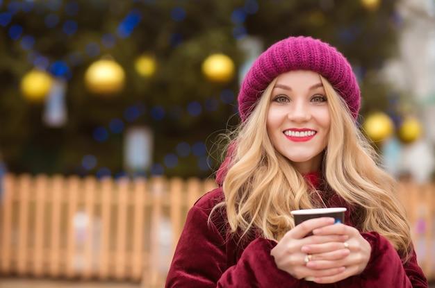 크리스마스 트리에서 커피를 마시는 긍정적인 금발의 여자