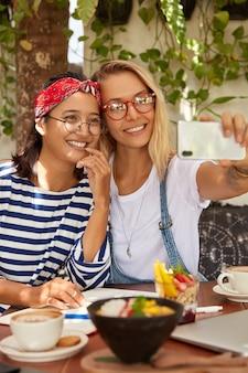 La donna bionda positiva tiene lo smart phone nelle mani, fa la foto del selfie insieme all'amico asiatico, goditi le vacanze estive insieme