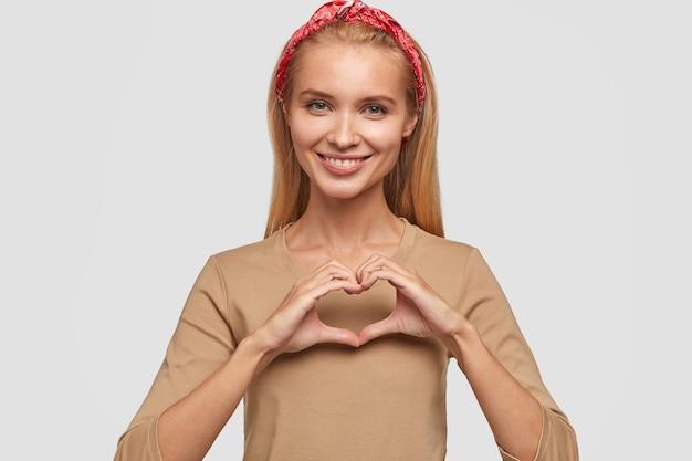 Positiva giovane donna bionda in posa contro il muro bianco