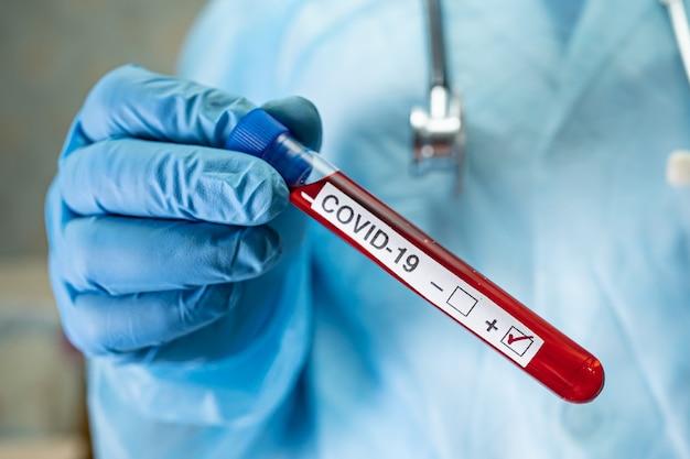 ラボでのcovid-19コロナウイルスの試験管内の陽性血液感染サンプル。入院中の患者をチェックして分析するために保持している科学者。