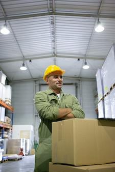 黄色いヘルメットをかぶったポジティブなブルーカラーの労働者で、腕を組んで笑っている箱の山に全体的に立っています。垂直ショット。労働概念