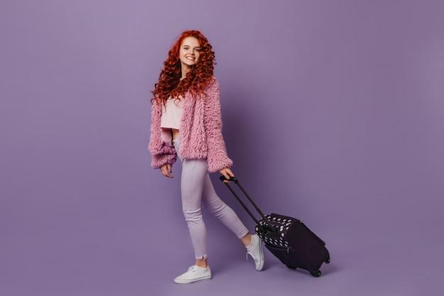 スタイリッシュな毛皮のコートと白いズボンに身を包んだ赤いカールのポジティブな青い目の女の子はスーツケースを運びます。