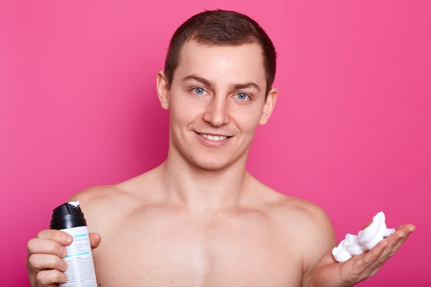 Positive blue eyed man carries bottle of shaving gel, poses with naked torso, showsc bare shoulders, muscles, has gentle smile, has smooth sking after shaving, isolated over pink.