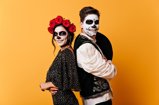 Positive boy and girl smile sincerely. photo of couple with halloween makeup in great mood on orange wall.