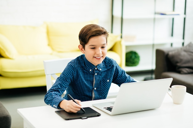 ラップトップの前に家に座って、現代の描画パッドを使用しながら興味を持っているように見える青いシャツを着たポジティブな男の子