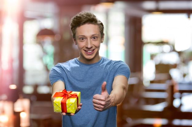 긍정적인 소년이 엄지손가락 제스처와 선물 상자를 보여주고 있습니다