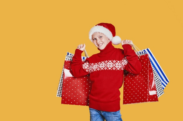 Positive boy in santa hat with presents