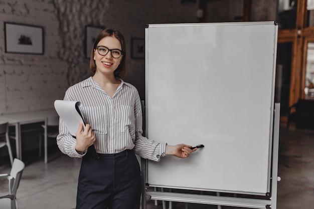 眼鏡とオフィス服を着たポジティブな茶色の目の女性がボードを指差して、書類と笑顔のフォルダーをカメラに持っています。