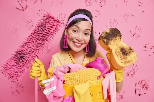 La casalinga asiatica bruna positiva sorride piacevolmente indossa orecchini con fascia per capelli guanti di gomma tiene mop e spugna sporchi soddisfatti dei risultati della pulizia della casa