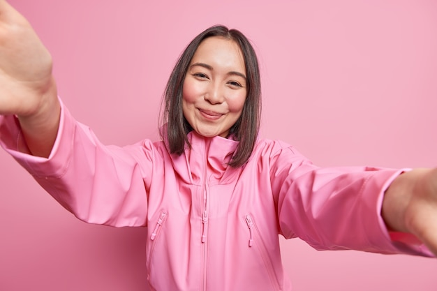 Positive brunette asian woman has tender gentle look smiles stretches arms poses for selfie wears jacket isolated over pink wall prepares to spend free time with friends.