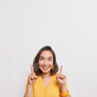 Positive brunette asian woman points above and smiles pleasantly wears yellow jumper earrings and bracelet isolated over white wall