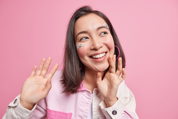 Positive brunette asian woman smiles broadly has perfect white teeth face decorated with shiny stones dreamy cheerful expression keeps hands up wears denim jacket isolated over pink wall
